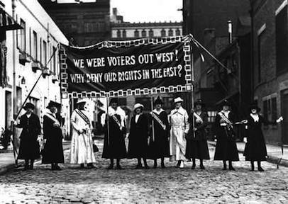 "Suffragists holding a sign that reads ""We were voters out west! Why deny our rights in the East?"""