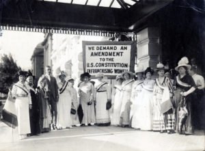 "Photograph of Senator Smoot with leading suffragists along with a sign that reads, ""We demand an amendment to the U.S. Constitution enfranchising women."""