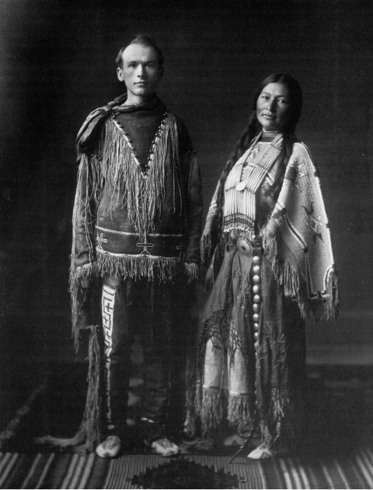 Black and white photo of Zitkala-Sa standing next to a man, and both are wearing traditional Native American clothing