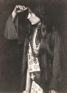 Black and white photo of Zitkala-Sa brushing her hair back and focusing on something out of sight. She wears traditional Native American clothing/jewelry.
