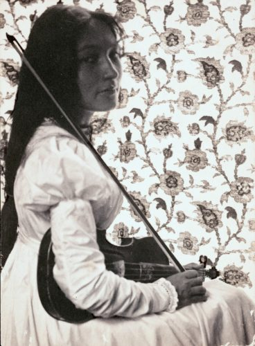 Photo of Zitkala-Sa sitting with her violin and bow against a floral wall. She wears a white dress.