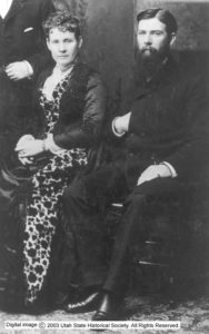 Black and white image of Franklin sitting near a woman in a floral dress.