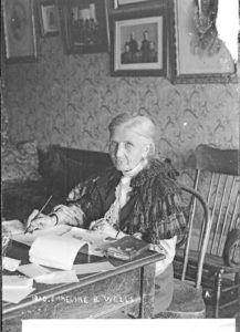 Black and white portrait of Emmeline B. Wells sitting at her desk