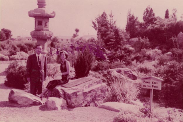 "Alice and Henry Kasai pictured among various boulders among trees and a tall stone sculpture. A sign in the foreground reads, ""Please stay on the path."""