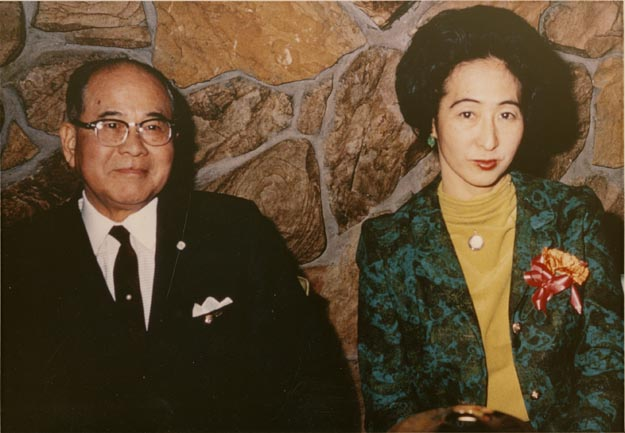 Henry, wearing a suit, and Alice, wearing a green turtle-neck and teal blazer, sitting against a rock wall.
