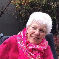 Barbara sitting outside in front of a tree wearing a hot pink sweater and floral scarf.