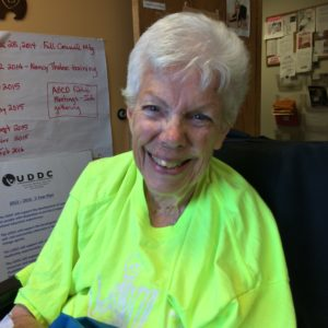 Image of an aging Barbara wearing a neon green t-shirt and smiling.