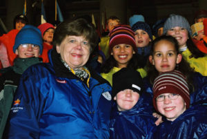 Olene smiles wearing a blue jacket while surrounded by diverse children wearing scarves, hats, and jackets.