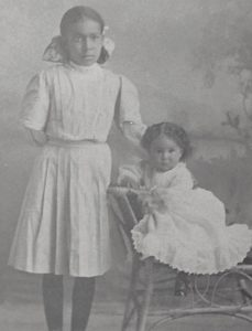 Black and white photo of a young Mignon standing next to her younger sister. Both are wearing dresses, and Mignon wears a bow in her hair.