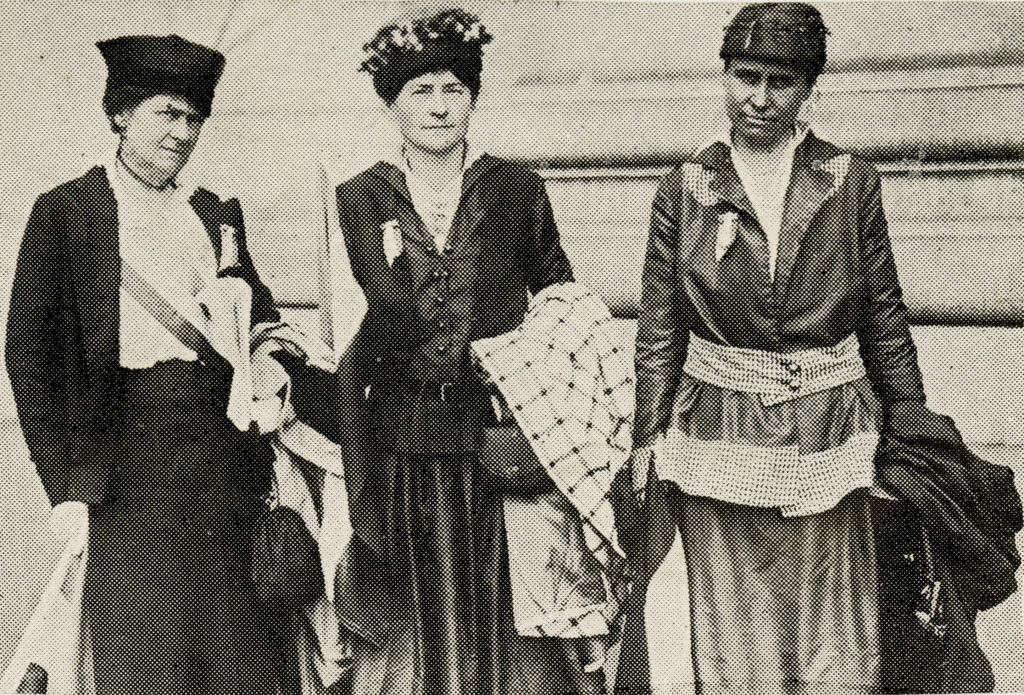 Black and white, old-style image of 3 women wearing dresses and hats carrying bags and coats.