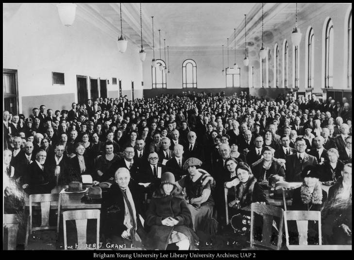 Black and white image of a full audience sitting in rows in an auditorium.
