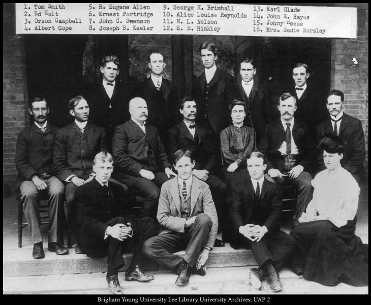 Black and white image of a group of 14 men and 2 women sitting in three rows wearing suits and dresses.