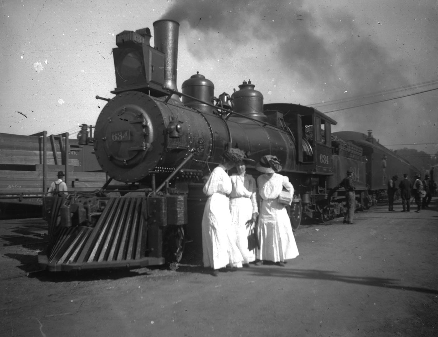 Three women in white dresses stand in front of a locomotive.
