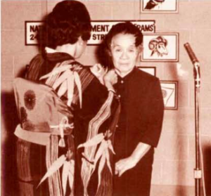 A woman in a kimono pins an award on another Japanese-American woman.