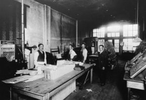 Photo of a newspaper print room with several men standing.