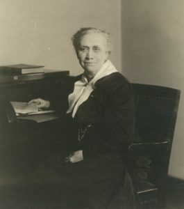 Photo of Elizabeth seated at a desk during her time in the state senate.