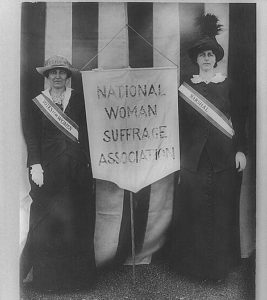 Two women pose with a National Woman Suffrage Association banner.