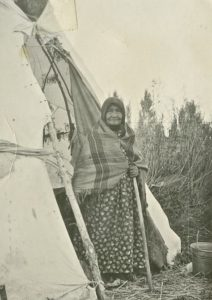 American Indian woman wrapped in a blanket stands outside a teepee.