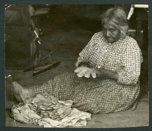 Woman making gloves.