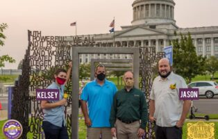 Artists and landscapers stand in front of the new sculpture in Salt Lake City on the grounds of the State Capitol.
