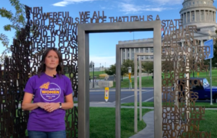 Woman stands in front of a bronze sculpture on the grounds of the Utah State Capitol
